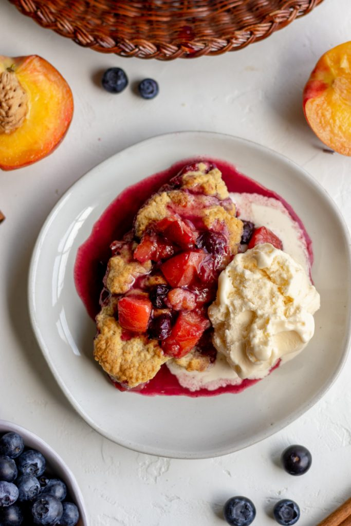 blueberry peach cobbler on a plate with ice cream